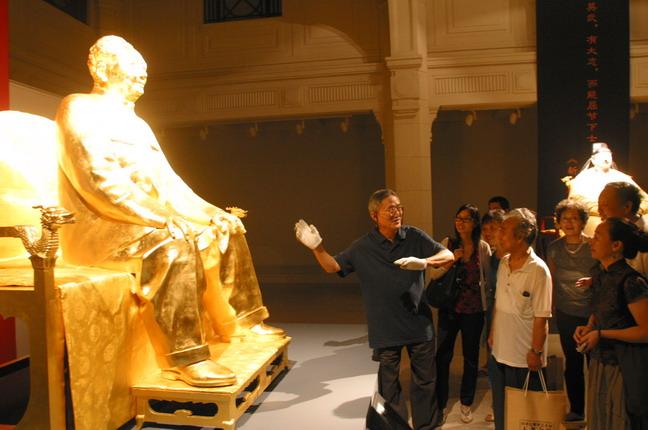 著名雕塑家田世信(左一)在展覽現場給幾位觀眾介紹藝術創作的感受。本報記者  方雲偉攝